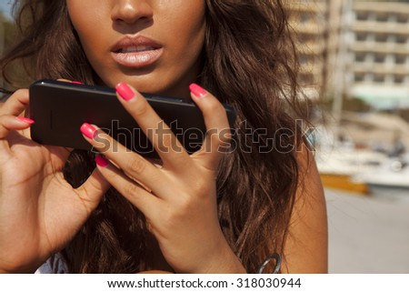 beautiful woman using her smart phone. Close up of lips and mobile. Fashion and technology. horizontal outdoors shot. - stock photo
