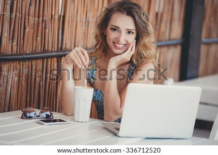 Beautiful woman using laptop at cafe. Young woman with coffee and laptop. Portrait of beautiful smiling woman sitting in a cafe with black laptop.
