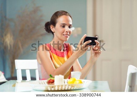 Beautiful woman using mobile phone at the table at home