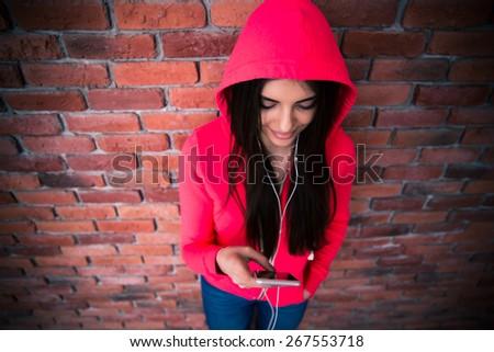 Beautiful woman using smartphone over brick wall - stock photo