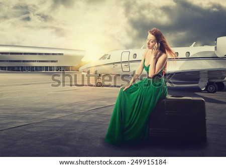 beautiful woman waiting for flight departure sitting on suitcase talking on mobile phone with airplane on background  - stock photo