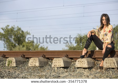 Beautiful woman waiting for the train on the old railroad - stock photo
