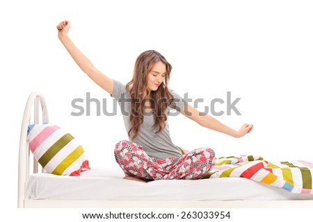 Beautiful woman waking up in the morning and stretching seated on a bed isolated on white background - stock photo