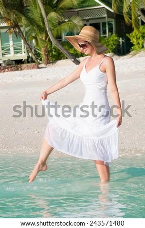 Beautiful woman walking along seaside on tropical beach - stock photo