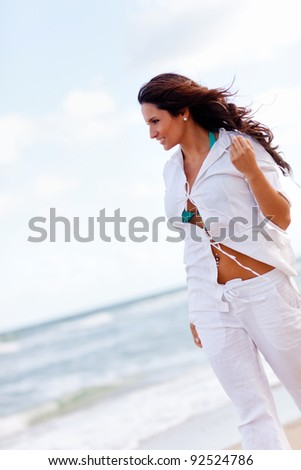 Beautiful woman walking at a peaceful beach - stock photo
