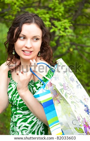 Beautiful woman walking at the summer park holding bags and looking away