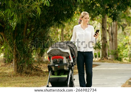 Beautiful woman walking down a lane in park with her little daughter in pushchair, text messaging on mobile phone and smiling. Full length view - stock photo