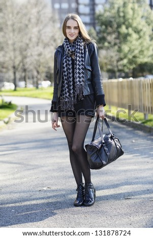 Beautiful woman walking in the city park - stock photo