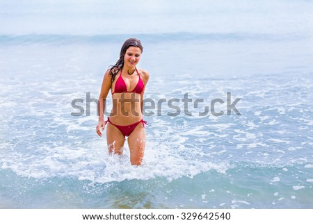 Beautiful woman walking in the Mediterranean sea in red swimming suit.