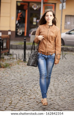 Beautiful woman walking on the street - stock photo