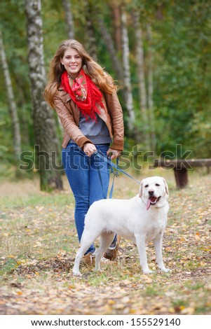 Beautiful woman walking with her dog in the forest