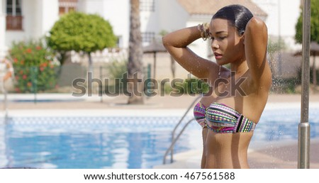 Beautiful woman washes near the pool on sunny day