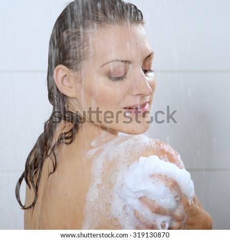 Beautiful woman washing her body shower gel - stock photo