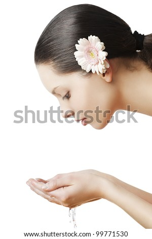 Beautiful woman washing her face isolated on white with wet hair and natural make up, she is turned in profile , looks the water in to her hands and has one flower in the hair - stock photo