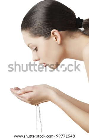 Beautiful woman washing her face isolated on white with wet hair and natural make up, she is turned in profile and looks the water in her hands - stock photo