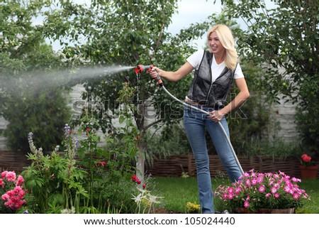 Beautiful woman watering garden - stock photo
