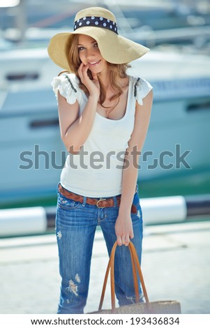 Beautiful woman wearing a hat at the sea - stock photo