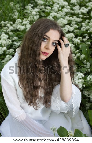 Beautiful woman wearing a long white dress sitting amongst white flowers holding her hand to her face - stock photo