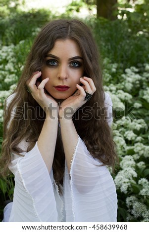 Beautiful woman wearing a long white dress sitting amongst white flowers holding her hands to her face - stock photo