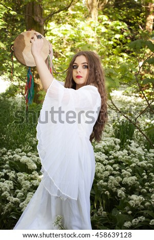 Beautiful woman wearing a long white dress standing in a forest holding a tambourine