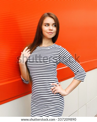 Beautiful woman wearing a striped dress in city over red background - stock photo