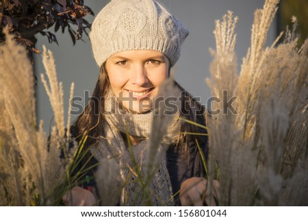 Beautiful woman wearing a warm knitted woolly cap standing smiling in a shaft of autumn sunlight as she enjoys a day of late Indian summer during the changing of the seasons - stock photo