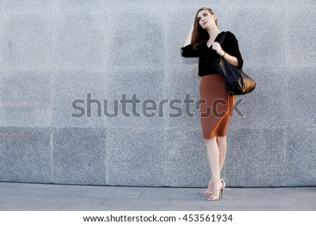 Beautiful woman wearing black blouse, brown pencil skirt and high heels shoes with leather bag posing at the evening city street. Vogue, female model - stock photo