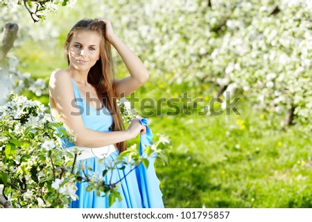 beautiful woman wearing blue dress  over spring orchard