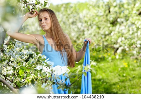beautiful woman wearing blue dress  over spring orchard - stock photo