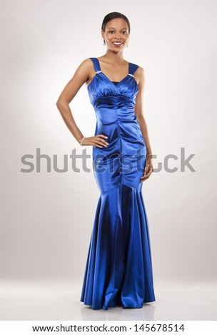 beautiful woman wearing blue evening dress on light background - stock photo