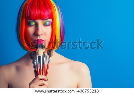 beautiful woman wearing colorful wig and holding make-up brushes against blue background - stock photo