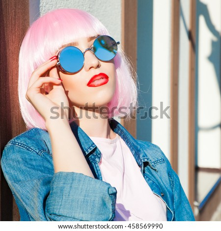 beautiful woman wearing colorful wig and silver sunglasses against street wall background