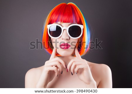 beautiful woman wearing colorful wig and white sunglasses against gray background - stock photo
