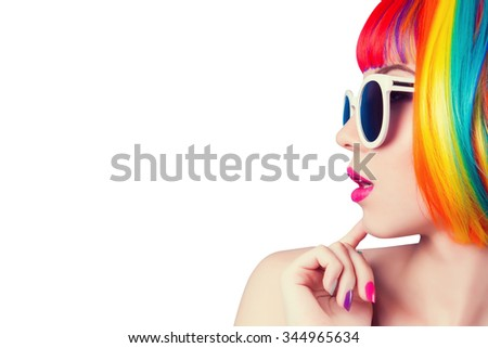 beautiful woman wearing colorful wig and white sunglasses against white background - stock photo