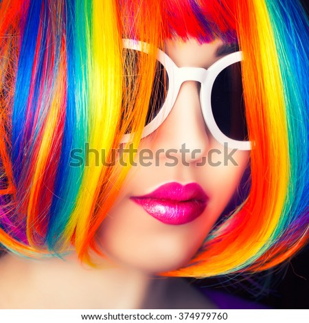 beautiful woman wearing colorful wig and white sunglasses against wooden background - stock photo