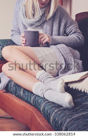 Beautiful Woman wearing  cozy sweater and Warm Wool Socks  reading a book sitting on comfortable sofa enjoying hot chocolate drink . Winter, Christmas  holidays concept. - stock photo