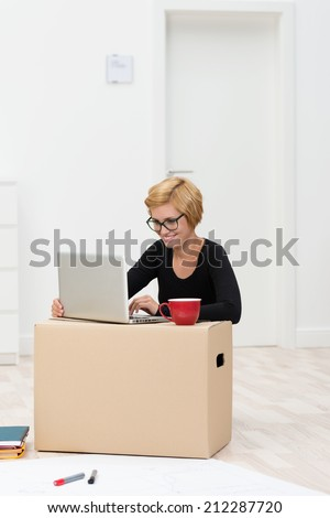 Beautiful woman wearing glasses using a carton as a desk for her laptop computer and mug of coffee as she moves into her new house - stock photo