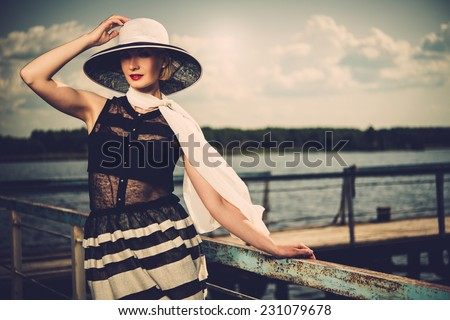 Beautiful woman wearing hat and white scarf sitting on old wooden pier - stock photo