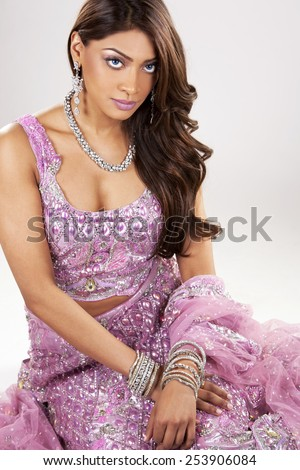 beautiful woman wearing indian traditional outfit on light background - stock photo