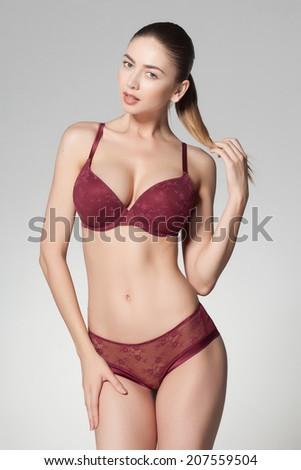 beautiful woman wearing lingerie on grey background - stock photo