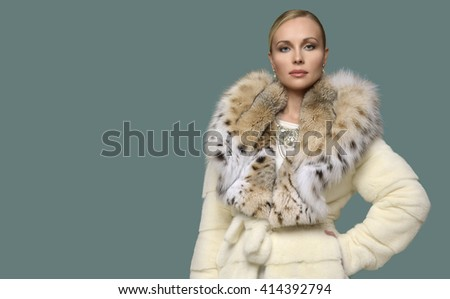 Beautiful woman wearing luxury white lynx fur coat. Winter fashion model.