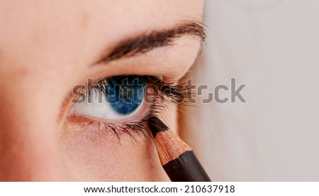 beautiful woman wearing makeup for blue eyes with eyeliner - stock photo