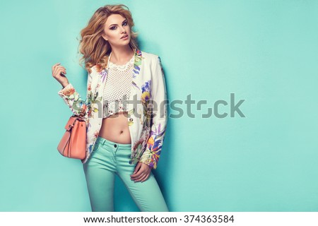 Beautiful woman wearing nice clothes, handbag posing on turquoise background. Fashion spring photo - stock photo