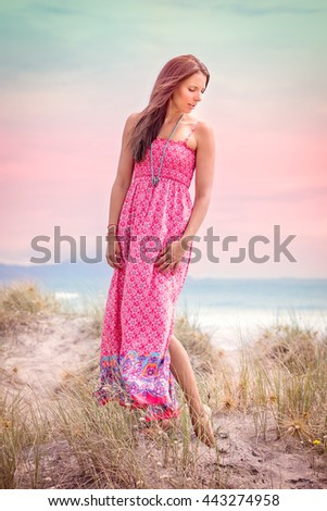 Beautiful woman wearing pink dress at beach - stock photo
