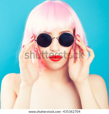 beautiful woman wearing pink wig and sunglasses against blue background - stock photo