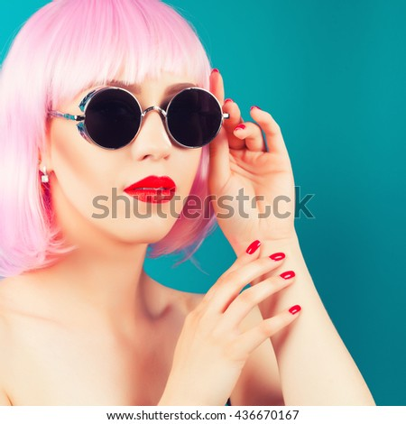 beautiful woman wearing pink wig and sunglasses against blue background