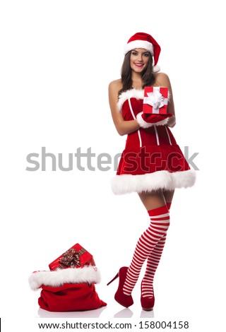 Beautiful woman wearing santa claus clothes holding christmas gift  - stock photo