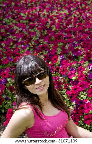 Beautiful woman wearing sun glasses with a background of purple flowers