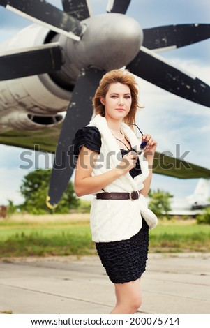 beautiful woman wearing sunglasses against plane