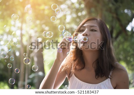 Beautiful woman wearing white dress blowing bubbles in the park,vintage style.